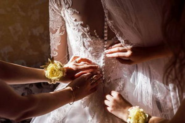 Bridesmaid helping bride fasten corset and getting her dress, preparing bride in morning for the wedding day.